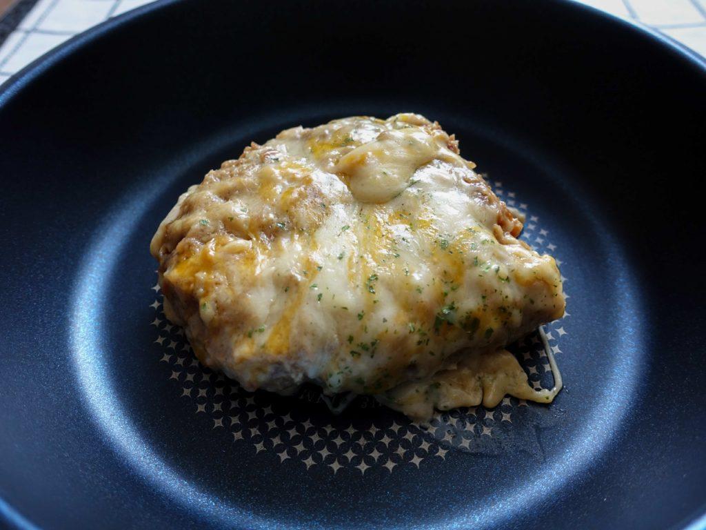 『松のやごちそうハンバーグ ホワイトガーリックチーズソース』を丸焼きにする為にフライパンに乗せた画像です。