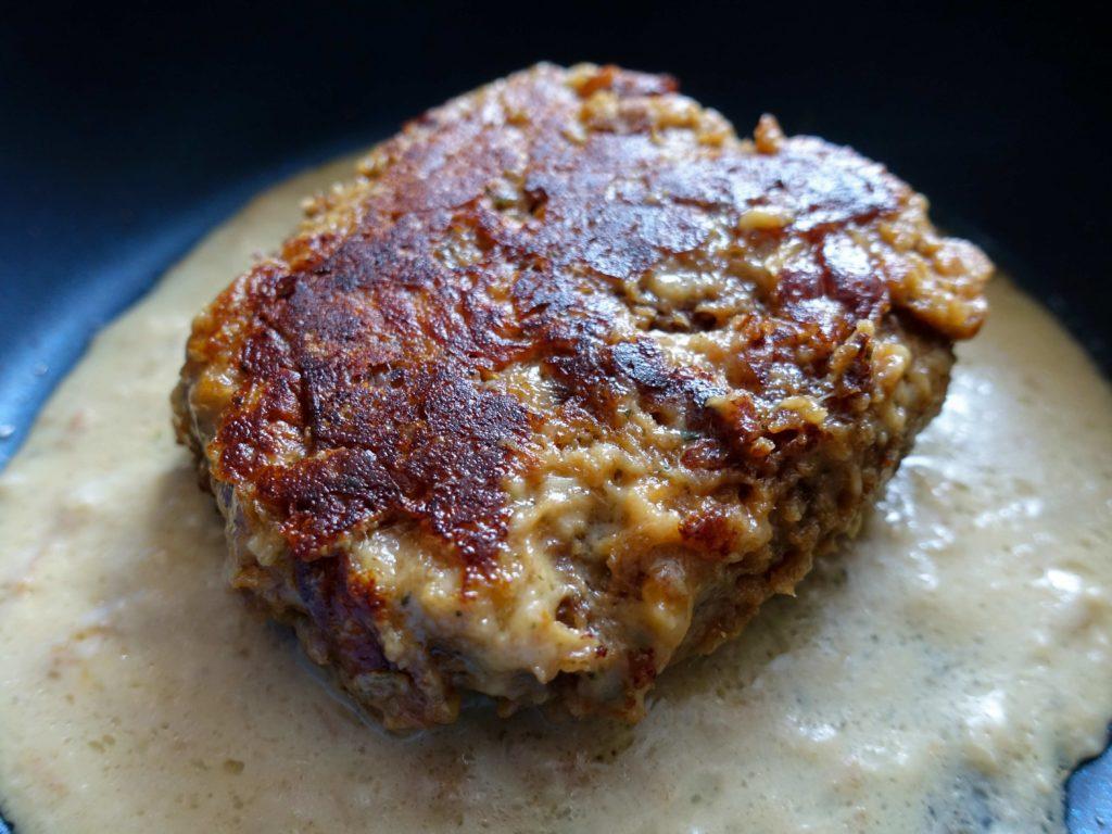 『松のやごちそうハンバーグ ホワイトガーリックチーズソース』がフライパンで焼きあがった画像です。 見た目が普通のハンバーグぽくなりました。